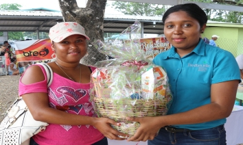 Aldesha Sanchez from Roaring Creek receiving basket of Belizean products, courtesy of Beltraide